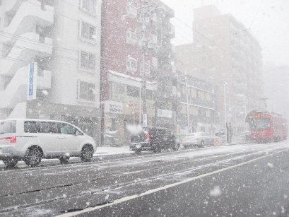 降雪中の札幌市街と路面電車